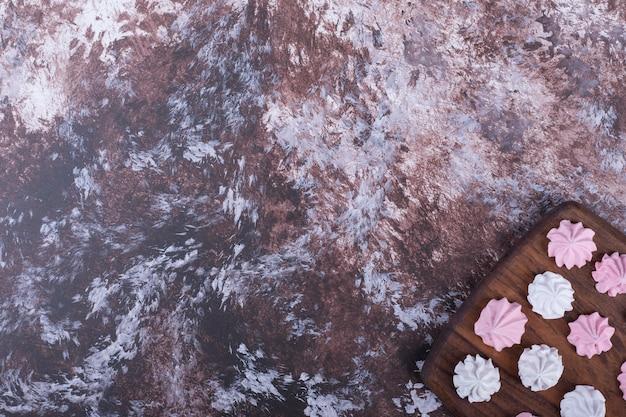 Witte en roze bloemvormige marshmallows op een houten schotel in de benedenhoek.