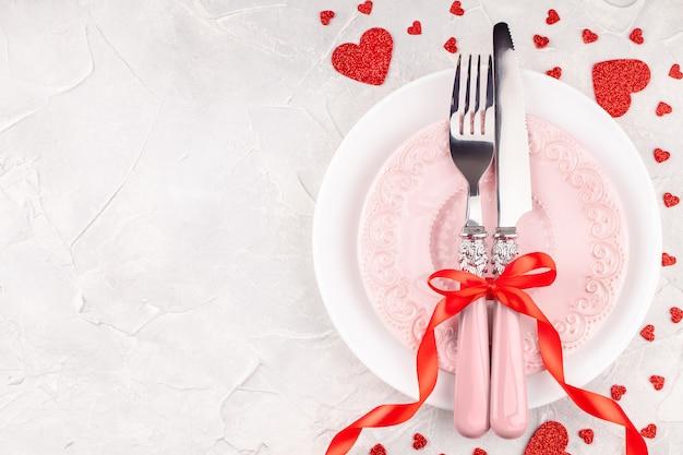 Witte en roze borden met vork, mes en rode strik met decoratieve harten