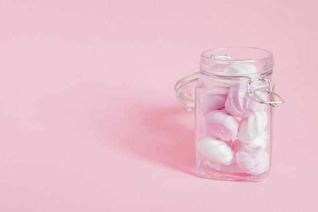 Witte en roze gedraaide schuimgebakjes in een glazen pot op roze