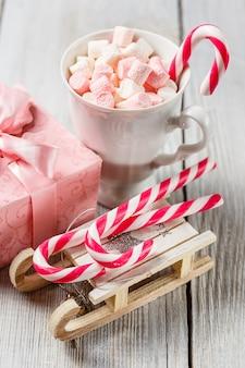 Witte en roze marshmallows in een beker, kerst zuurstokken en speelgoed slee op witte tafel.