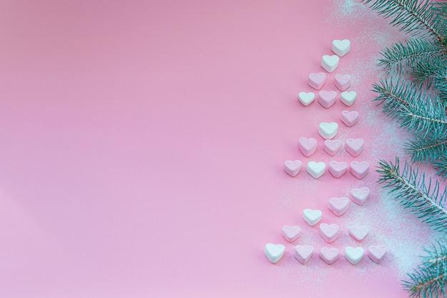 Witte en roze marshmallows op een roze achtergrond in de zijkant van een kerstboom