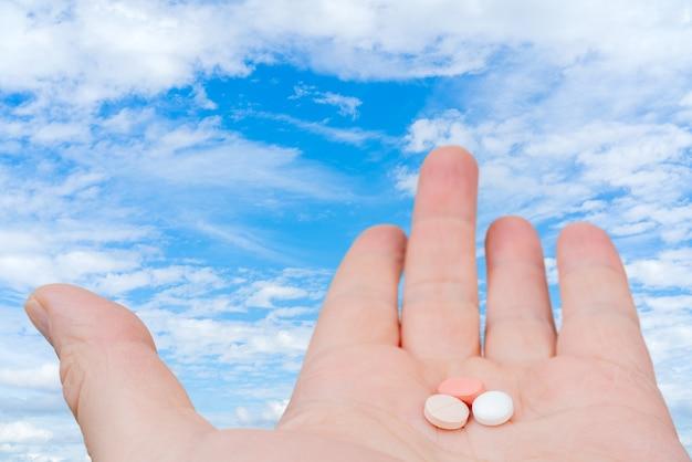 Witte en roze pillen in de palm van je hand. behandeling met pillen.