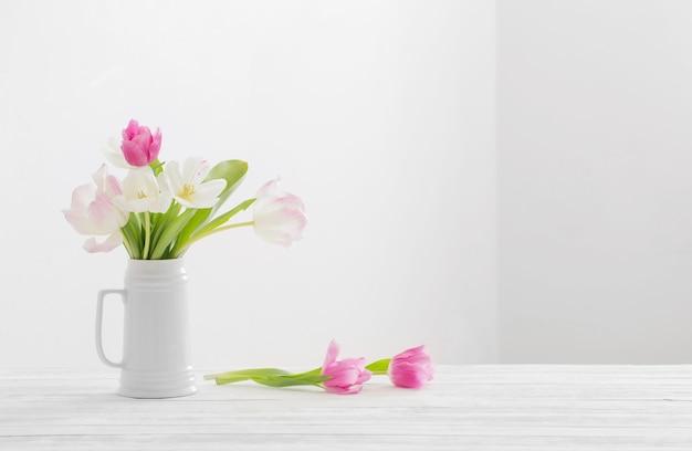 Witte en roze tulpen in kruik op witte achtergrond