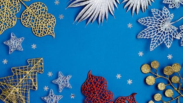 Witte en zilveren versieringen plat op een klassieke blauwe achtergrond met kopieerruimte. kerstachtergrond in kleur klassiek blauw met witte en zilveren ornamenten, kerstachtergrond met verlanglijstje