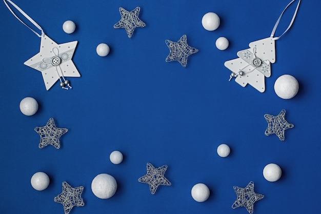 Witte en zilveren versieringen plat op een klassieke blauwe achtergrond met kopieerruimte