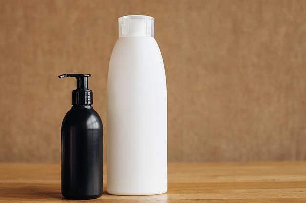 Witte en zwarte plastic fles met handdesinfecterend middel op een beige achtergrond. lichaamscosmetica. coronavirus-preventie, bescherming van handhygiëne tegen het kroonvirus