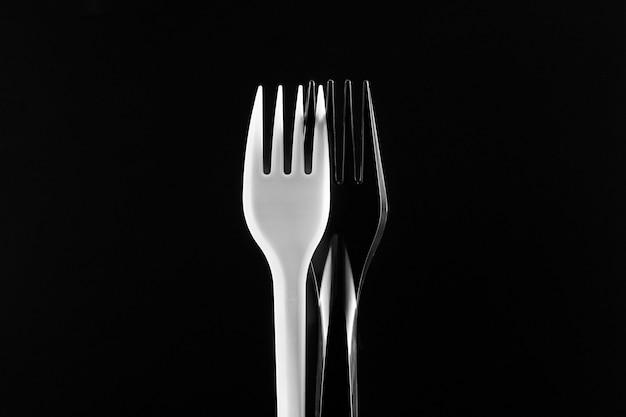 Witte en zwarte plastic vorken op een zwarte achtergrond. de zwarte vork zit iets achter de witte.