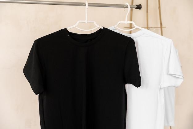 Witte en zwarte t-shirts op hangers voor ontwerppresentatie