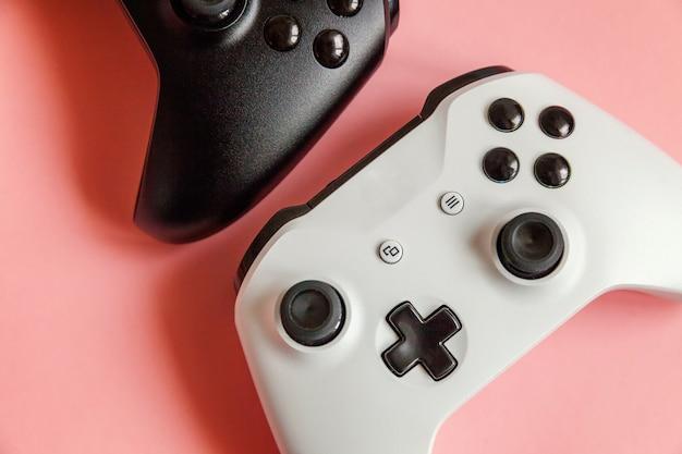 Witte en zwarte twee joystick gamepad, gameconsole op pastel roze achtergrond