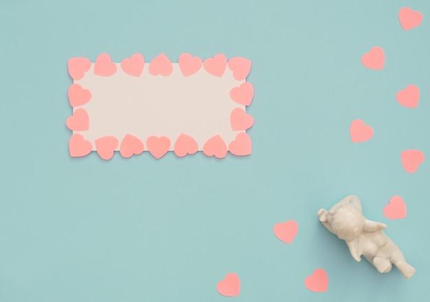 Witte engel en blanco vel met roze harten frame op blauwe achtergrond.