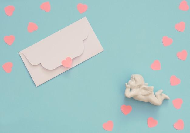 Witte engel, envelop en veel roze harten op blauwe achtergrond.