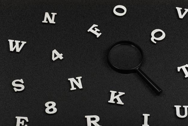 Witte engelse letters en cijfers en vergrootglas op zwart.