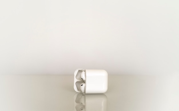 Witte enkele draadloze hoofdtelefoon in oplaaddoos op grijs verloop met reflectie in het glas van de tafel
