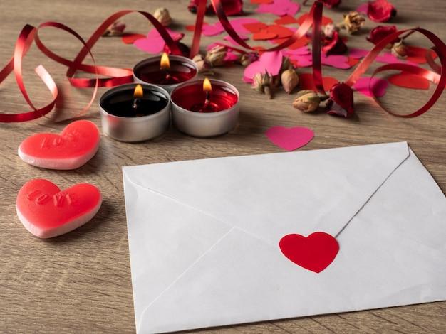 Witte envelop naast kaarsen met rode rozenblaadjes en harten op tafel