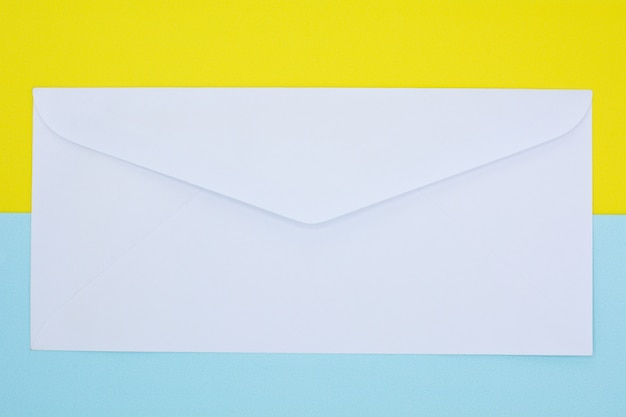 Witte enveloppost op blauwe en gele achtergrond