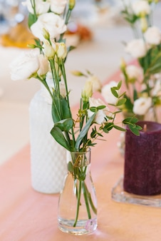 Witte eustoma bloemen in glazen transparante vaas in bruiloft of banket tafeldecor