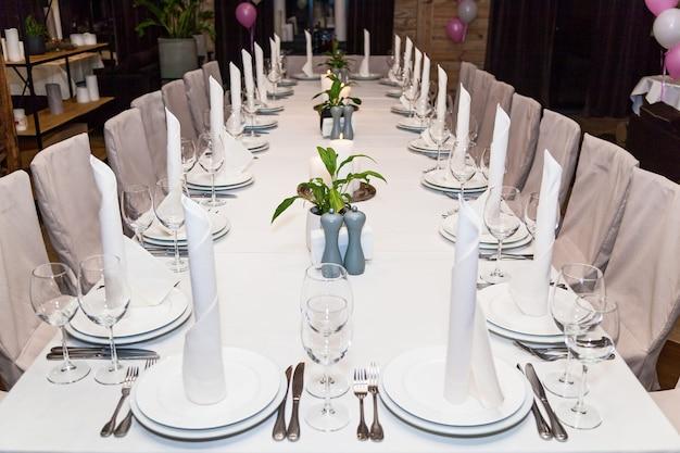 Witte feestelijke tafel met kaarsen voor het diner. bankettafel