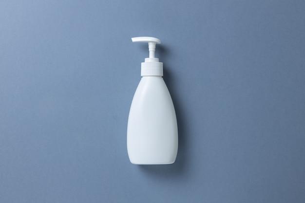 Witte fles met handzeep, douchegel of bodycrème op grijze achtergrond