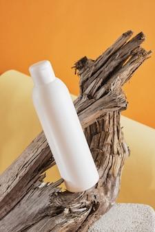 Witte fles op een betonnen podium tegen een achtergrond van houten drijfhout, bruine achtergrond