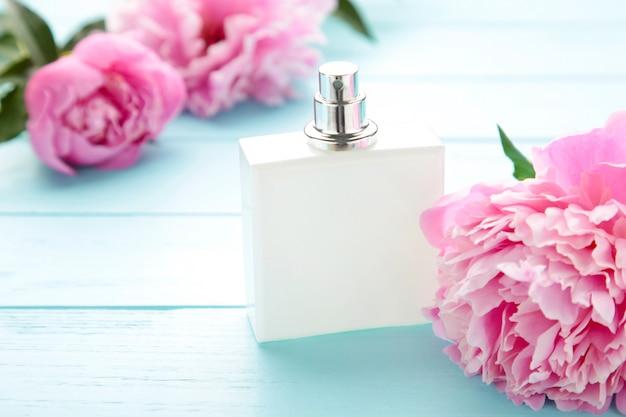 Witte fles parfum met roze bloemen op roze