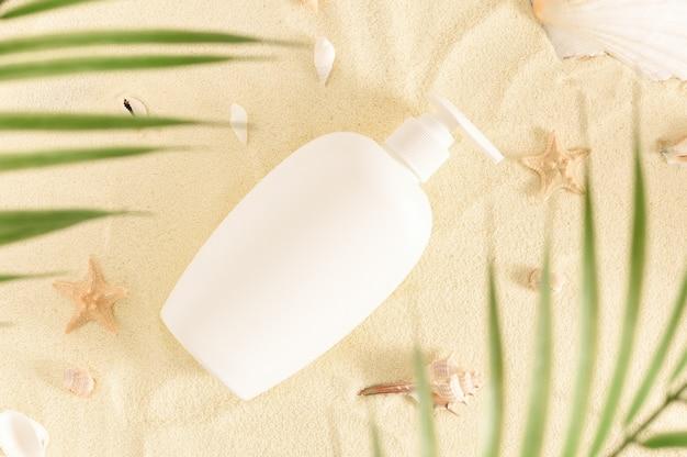 Witte fles zonnebrandolie op wit zand met schelpen