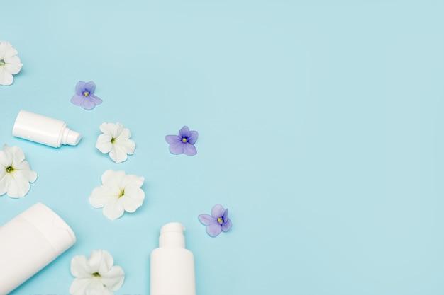 Witte flessen met dispenser met lege ruimte voor tekst op delicate blauwe achtergrond, mockup. kopieer de ruimte, plat leggen
