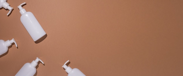 Witte flessen met een dispenser liggen op een bruine kartonnen ondergrond. bovenaanzicht, plat gelegd. banier.