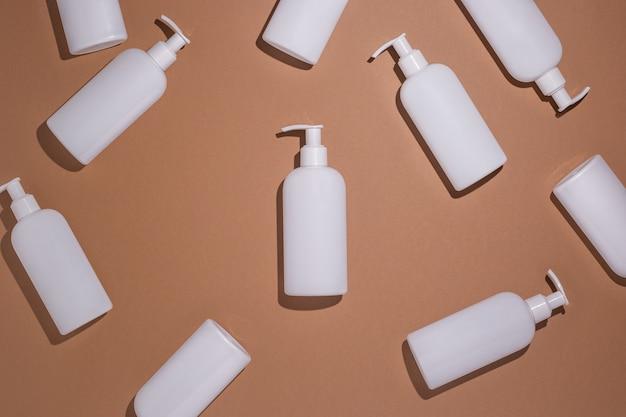 Witte flessen met een dispenser liggen op een bruine kartonnen ondergrond. bovenaanzicht, plat gelegd.