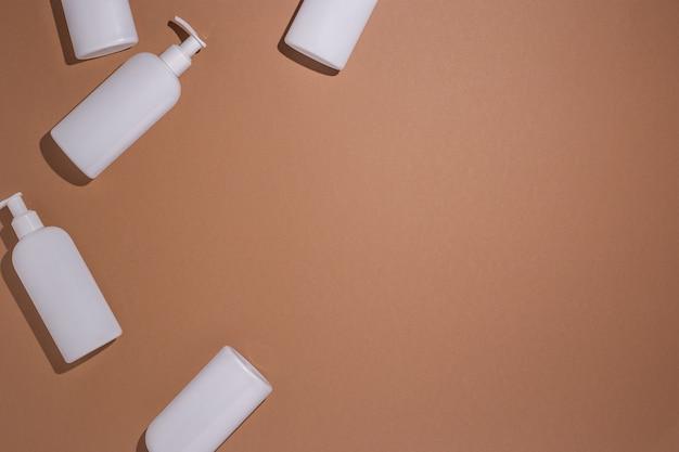 Witte flessen met een dispenser liggen op een bruine kartonnen ondergrond. bovenaanzicht, plat gelegd. Premium Foto