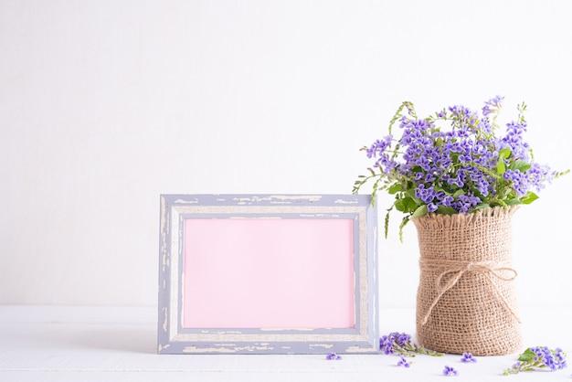 Witte fotolijst met mooie paarse bloem in vaas op witte houten tafel.