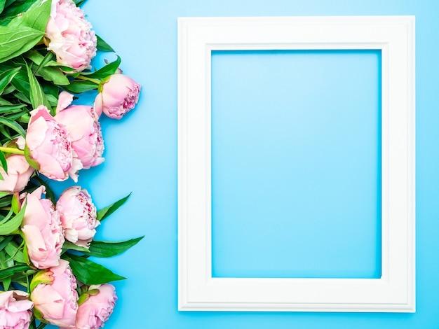 Witte fotolijst met roze pioenrozen en groen op een blauwe achtergrond