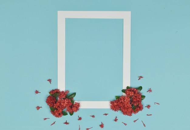 Witte fotolijst versierd met rode spijkerbloemen aan de zijkant.