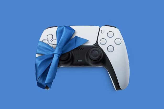 Witte gamecontroller van de volgende generatie, verpakt in lint. ideaal als cadeau van de kerstman met kerst.