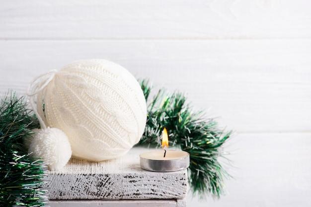Witte gebreide kerstbal en decoratie met brandende kaars in wit scandinavisch interieur
