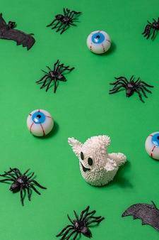 Witte geest met spinnenoogbollen en vleermuizen op groene achtergrond