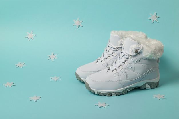 Witte geïsoleerde dames wintersneakers met sneeuwvlokken. sportschoenen voor de winter.