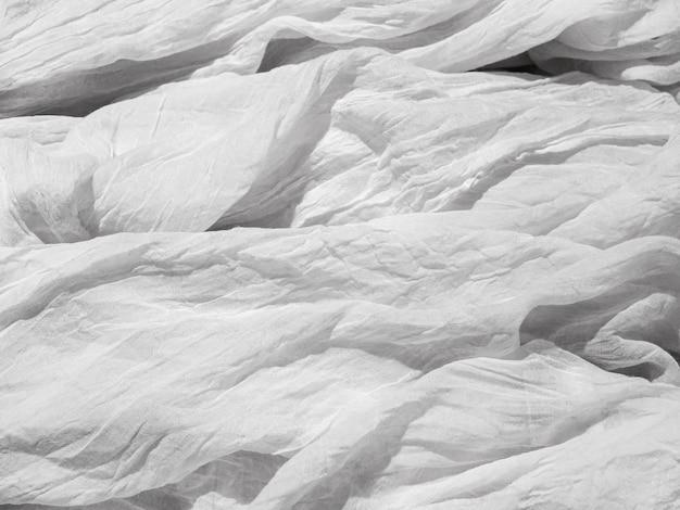 Witte gekreukte verfrommelde lichte stof op het bed de textuur van de stof lay-out voor de poster