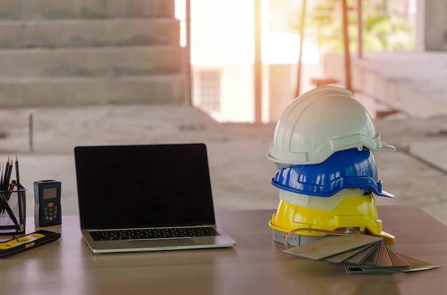 Witte, gele en blauwe harde veiligheidshelm voor de stapel van het veiligheidsongeval met laptopcomputer en hulpmiddelen op werkplaatsbureau bij in bouwwerfbouw
