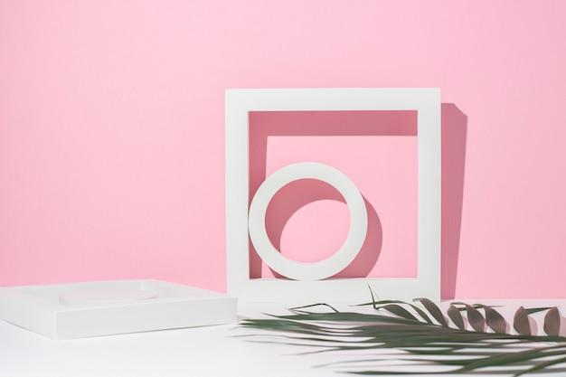 Witte geometrische podia voor presentatie en een blad van een palmboom op een witroze achtergrond.