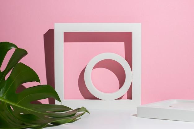 Witte geometrische podia voor presentatie en monsterablad op wit roze achtergrond.