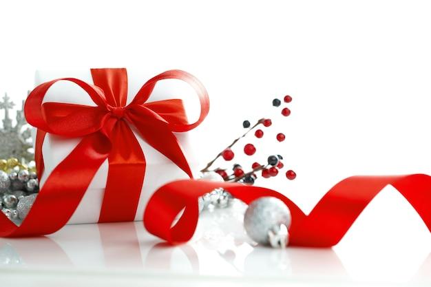 Witte geschenkdoos gebonden rood lint boog en kerstballen