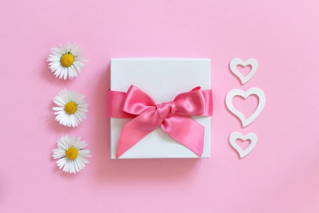 Witte geschenkdoos, margrieten en harten op een lichtroze bovenaanzicht als achtergrond