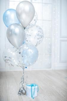 Witte geschenkdoos met blauw lint en ballon in lichte kamer. minimaal kerstnieuwjaarsconcept. verjaardagscadeau