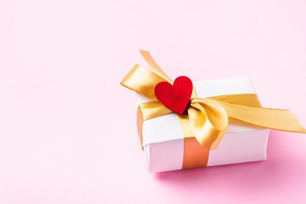 Witte geschenkdoos met een gouden striklint en houten rode harten
