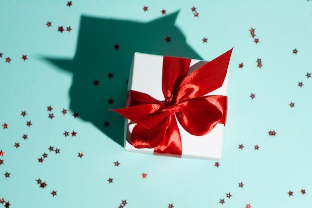 Witte geschenkdoos met een rood lint en een verstrooiing van sterren op mint achtergrond. de schaduw is als een huis.