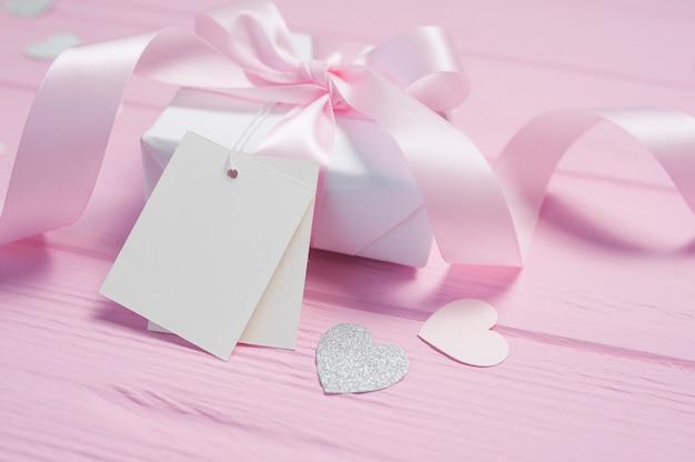 Witte geschenkdoos met een roze satijnen strik en lint op roze houten achtergrond. valentijn kaart