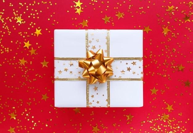 Witte geschenkdoos met gouden strik en sterren o