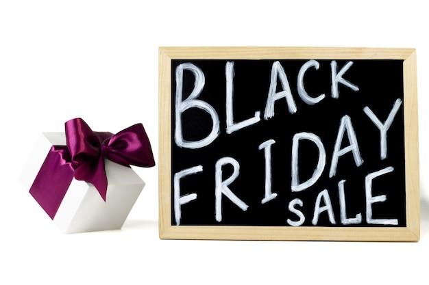 Witte geschenkdoos met lila lint naast black friday sale teken, op witte achtergrond
