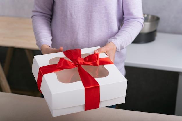 Witte geschenkdoos met rode strik in vrouwelijke handen