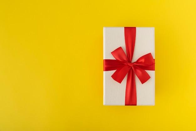 Witte geschenkdoos met rode strik op gele achtergrond. kopieer ruimte.